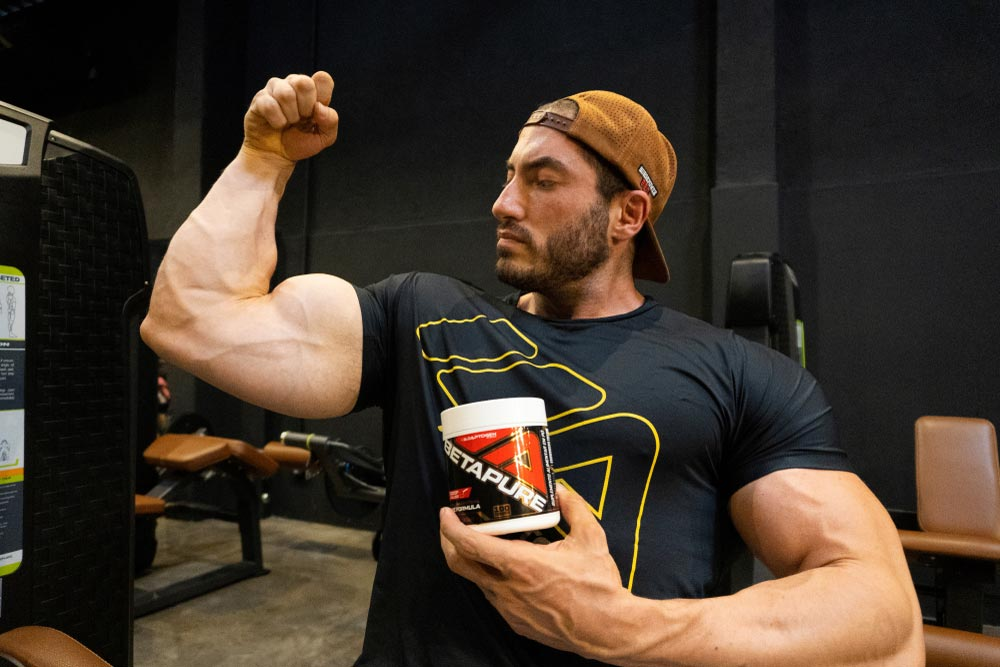Pessoa encolhendo o braço demonstrando que está fazendo força, em suas mãos um pote de BetaPure