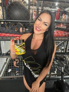 """Pessoa sorrindo de cabelos longos usando uma camisa preta escrito """"Adaptogen"""", e segura em suas mãos um pote de Creatina HD Cret de limão"""